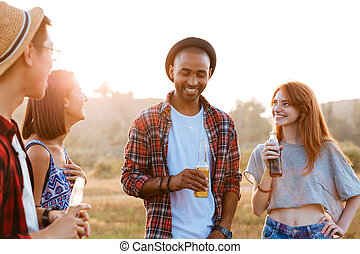 Smiling young friends standing and talking outdoors