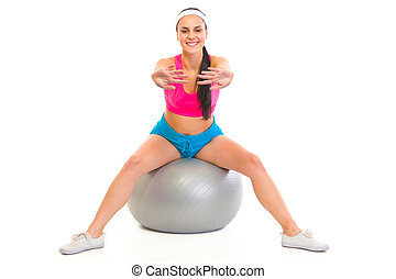 Smiling young girl doing exercises on fitness ball isolated on white