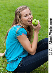 Smiling young girl eating a delicious green apple while looking towards the side