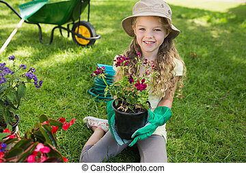Smiling young girl engaged in gardening