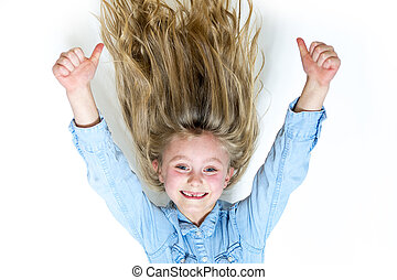 Smiling young girl hanging in front of white background