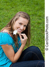 Smiling young girl holding a flower next to her face