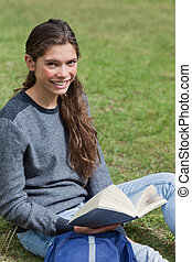 Smiling young girl holding an open book while sitting down on the grass in a park