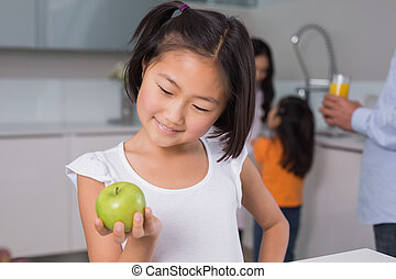 Smiling young girl holding apple with family in at kitchen