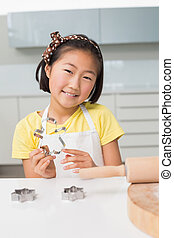 Smiling young girl holding cookie mold in kitchen