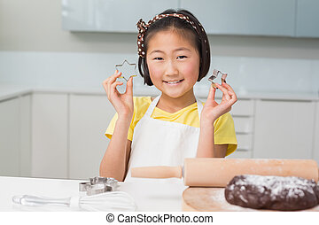Smiling young girl holding cookie molds in kitchen