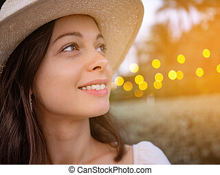 Smiling young girl in a hat outdoors