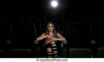 Smiling young girl in cinema a bucket of popcorn