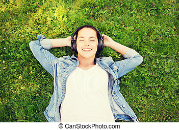 smiling young girl in headphones lying on grass