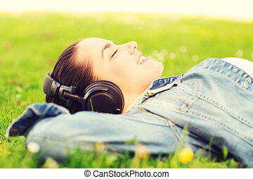 smiling young girl in headphones lying on grass - lifestyle,...