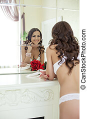Smiling young girl in lingerie posing near mirror