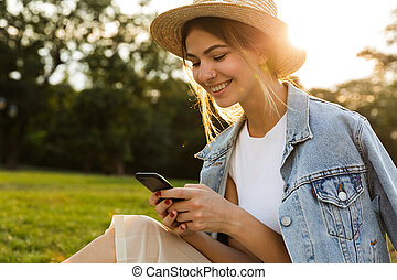 Smiling young girl in summer hat sitting outdoors