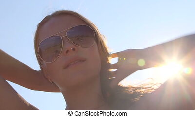 Smiling young girl in sunglasses on beach in the sun