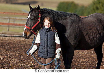 Smiling young girl leading her horse - Smiling young girl...