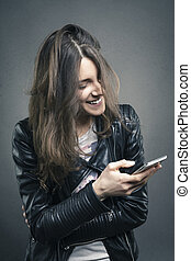 Smiling young girl looking at phone with amused emotion on her face