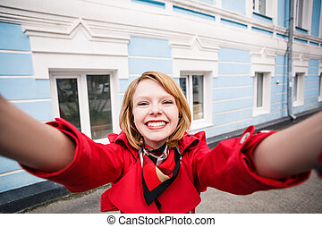 Smiling young girl making selfie