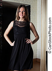 Smiling young girl posing in black cocktail dress