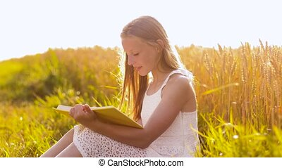 smiling young girl reading book on cereal field - country,...