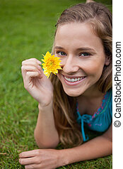 Smiling young girl showing a beautiful yellow flower while lying on the grass in a park