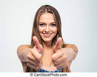 Smiling young girl showing thumbs up