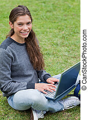 Smiling young girl sitting down on the grass in a park while typing on her laptop
