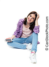 Smiling young girl sitting on the floor with smartphone