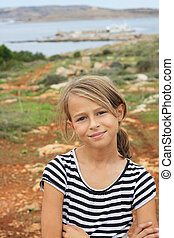 Smiling young girl standing on a view point