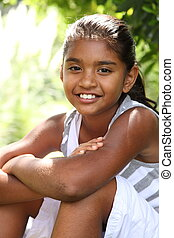 Smiling young girl under a tree - Young girl relaxing in the...