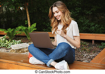 Smiling young girl using laptop computer while sitting