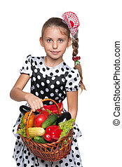 Smiling young girl with a basket of vegetables