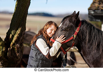 Smiling young girl with a dark bay horse - Portrait of a...