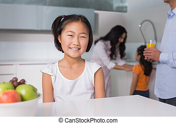 Smiling young girl with family in the background at kitchen