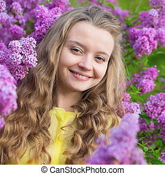Smiling young girl with lilac blossom
