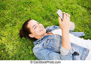 smiling young girl with smartphone lying on grass -...