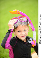 smiling young girl with swimming goggles and snorkel
