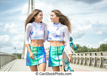 Smiling young girls with skateboard posing outdoor.