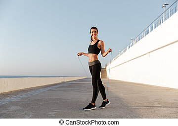 Smiling young happy sports woman make sport exercises