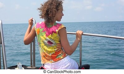 smiling young happy woman sitting in going cutter looks at sea