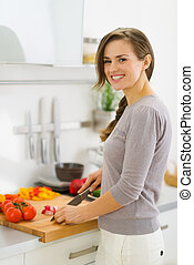 Smiling young housewife cutting vegetables on salad in kitchen