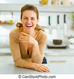 smiling young housewife in modern kitchen