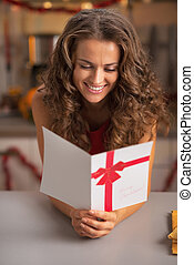 Smiling young housewife reading christmas postcard in kitchen