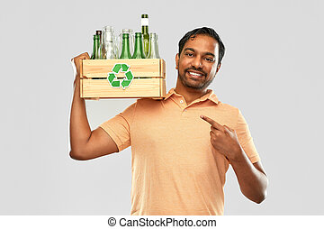 smiling young indian man sorting glass waste