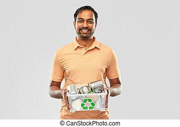 smiling young indian man sorting metallic waste