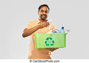 smiling young indian man sorting plastic waste