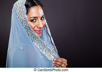 young indian woman in sari on black background