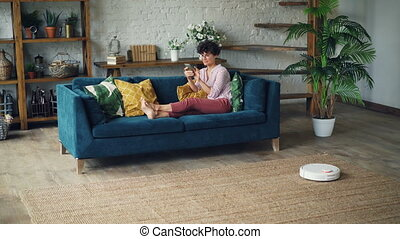 Smiling young lady house owner is sitting on sofa in living...