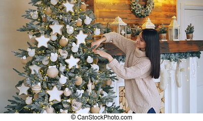 Smiling young lady is decorating Christmas tree with balls,...