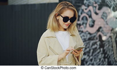 Smiling young lady is using smartphone browsing or chatting onine standing outdoors in modern city with graffiti in background. Girl is wearing sunglasses and coat.