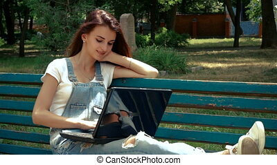 smiling young lady lying on the bench with a laptop