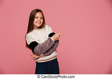 Smiling young lady pointing at copy space and looking camera